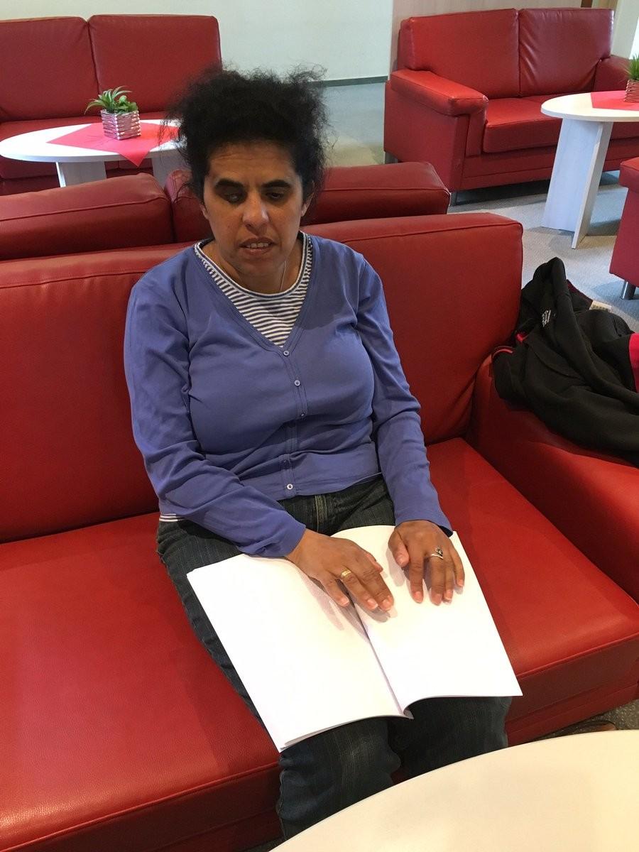 Lydia sitzt auf einem Sofa und liest ein Buch in Braille.