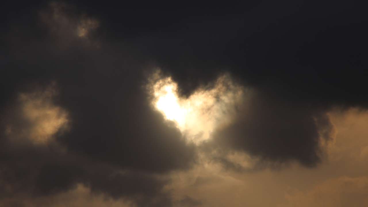 A break in dark clouds with sunlight shining through that almost looks like a heart