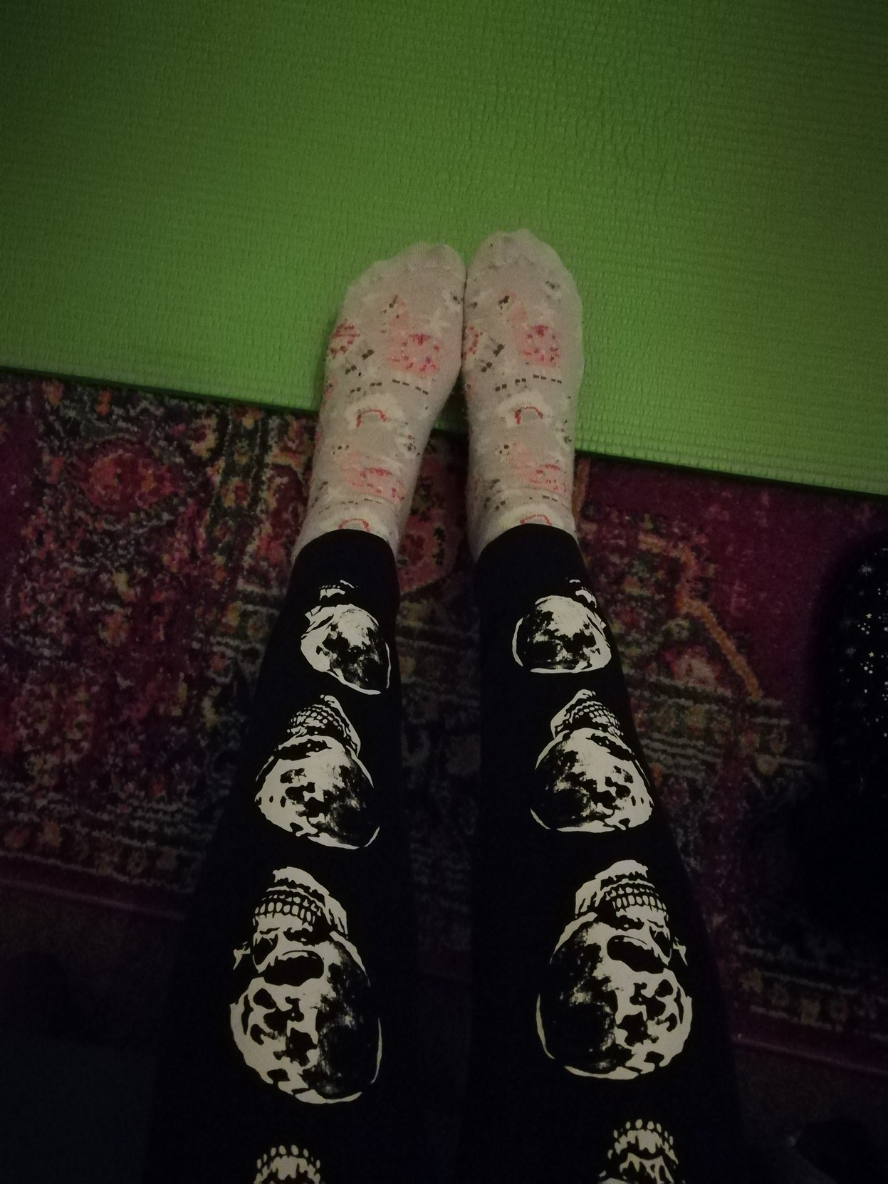 my legs that are black with moon skulls, contrasting with my socks which are lilac with pink and white llamas