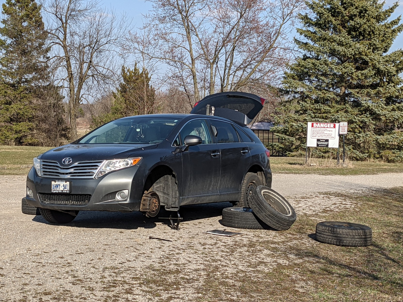My car, up on a jack, one winter tire removed in anticipation of the summer tire