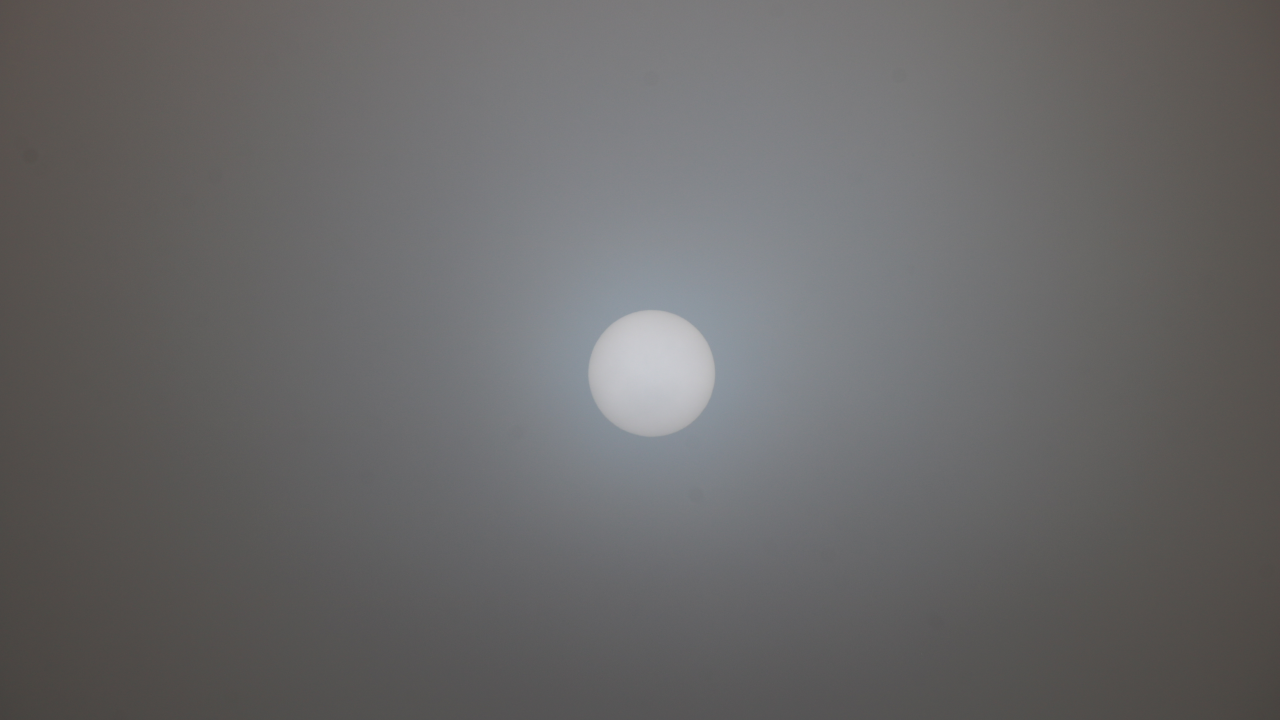 The sun, visible through a cover of fog