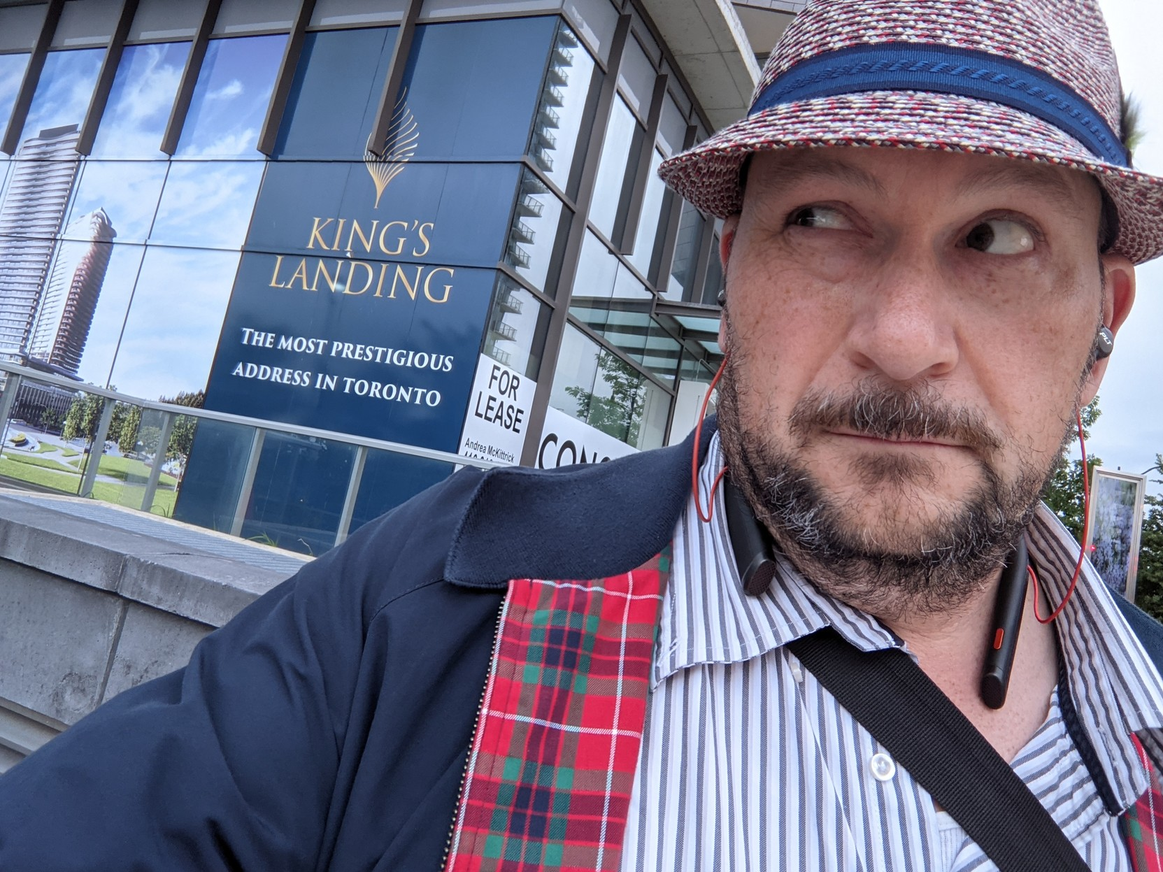 """Selfie of self looking very dapper, but giving side-eye to a Toronto condo development under construction, titled """"King's Landing"""""""