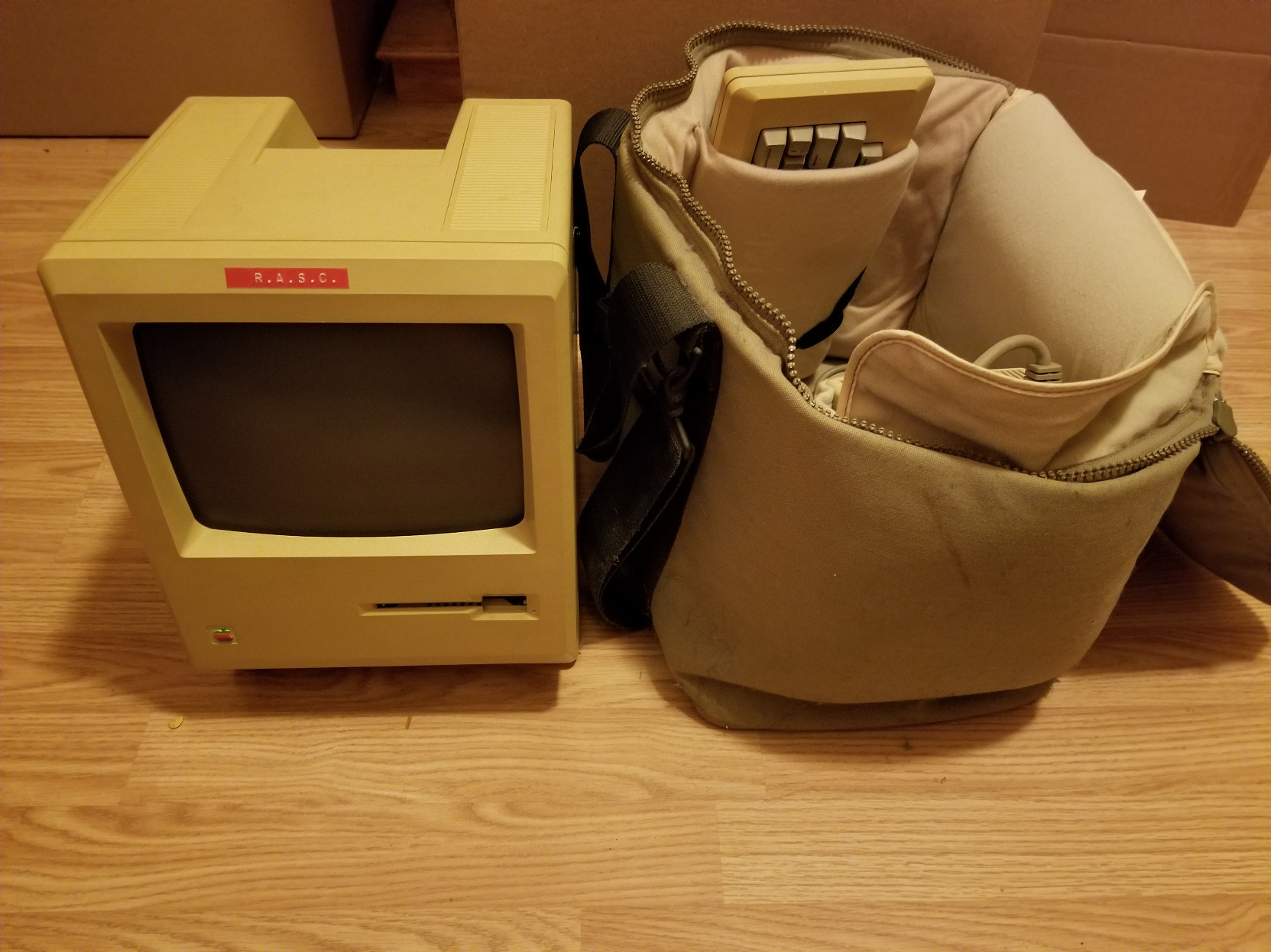 An original-style Mac next to an open carrying case, which also has the keyboard and external disk drive (and the mouse, not seen). The Mac has a piece of tape with R.A.S.C. stamped on it.